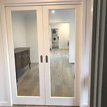 double doorway openings between entry and lounge, duplicating same door system between lounge and kitchen space. Single glazed ensures minimal light or viewing restriction.