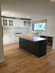 Hampton style kitchen with dual colour cabinetry combination; dual benchtop finishes; subway tiles; servery window and engineered boards