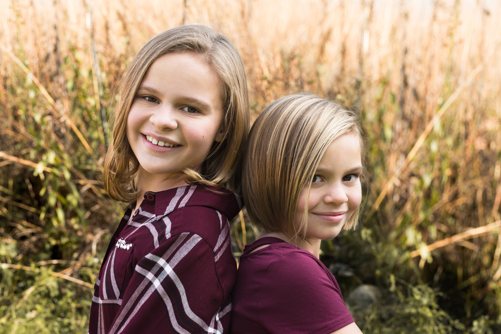 Kids smiling back to back in a field