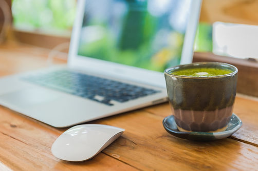cup of matcha green tea with laptop comp