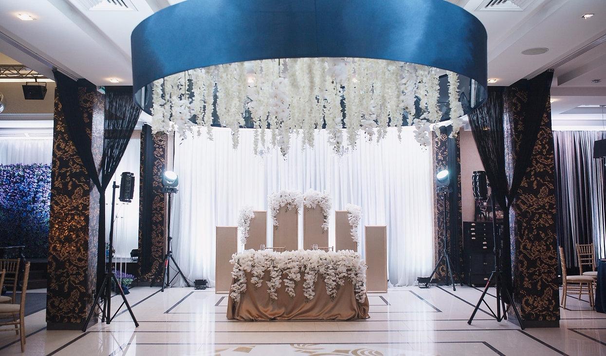 свадебный стол молодоженов, свадебная зона за столом молодоженов усыпанная белоснежными цветами , зона молодоженов в золотых синих и белых цветовых решениях создавала команда wpdecor из Тюмени. Красивейшая фотография с невероятно красивым и стильным декором , где создана величествнная люстра из цветов с синим абажуром, красивый свет и идеальное сочетание свадебного стиля. ресторан винтаж Тюмень. Свадебное агентство Wedding Production выгодно отличается от других свадебных агентств Тюмени. Команда Ксении Стан WP и студия декора WPdecor studio постарались на славу.