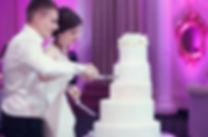 молодожены режут свадебный торт на белоснежной свадьбе от свадебного агентства wedding production сайт wpwedding.com