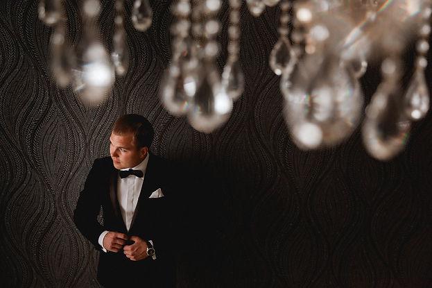 красивая свадебная фотография Тюмень, жених готовится к встрече с будующей супругой, красивый смокинг, блестящая люстра, и шикарная фотография от команды свадебного агентства wedding Production