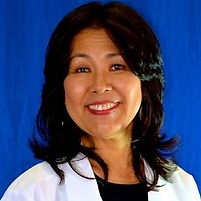 Yoko Fujimaki in a white lab coat in front of a blue background