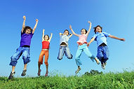 Children jumping on grass