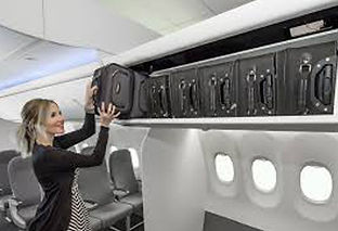 Woman putting luggage in overhead compartment on airplane