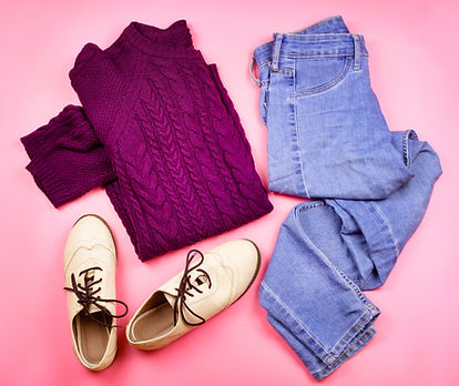 Clothes and shoes layed out on pink background