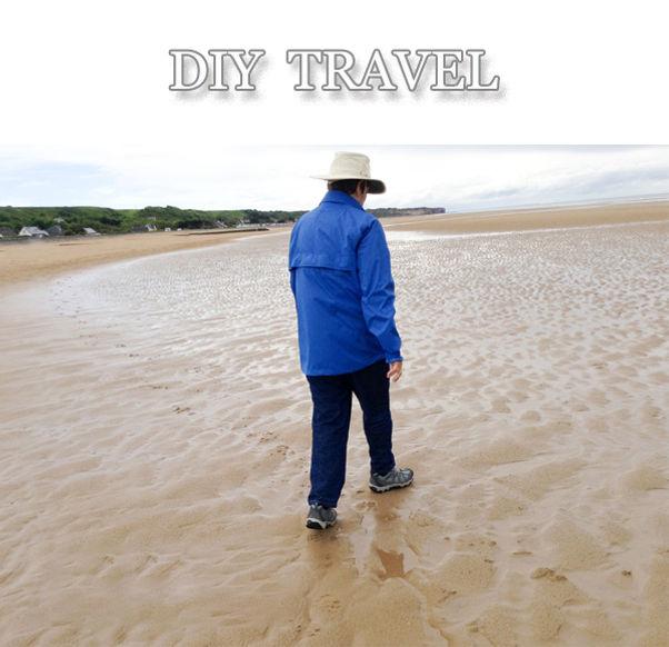 Solitary woman walking Normandy Beach