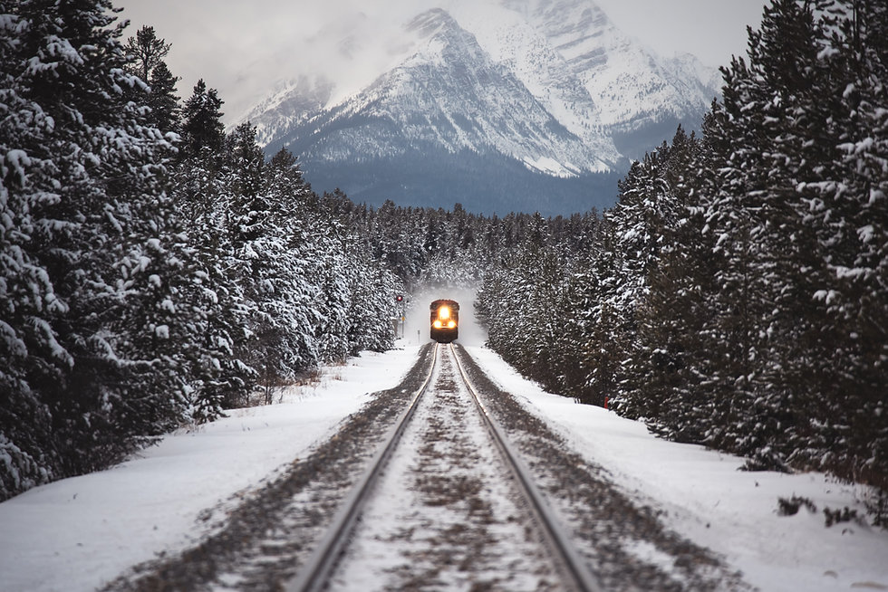 Locomotive at the foot of a snowy mountain approaching the camera.
