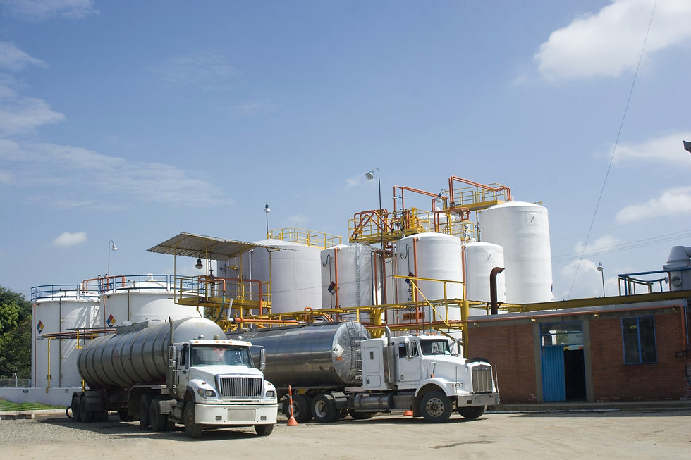 Tanker trucks parked outside of a plant awaiting to be loaded.