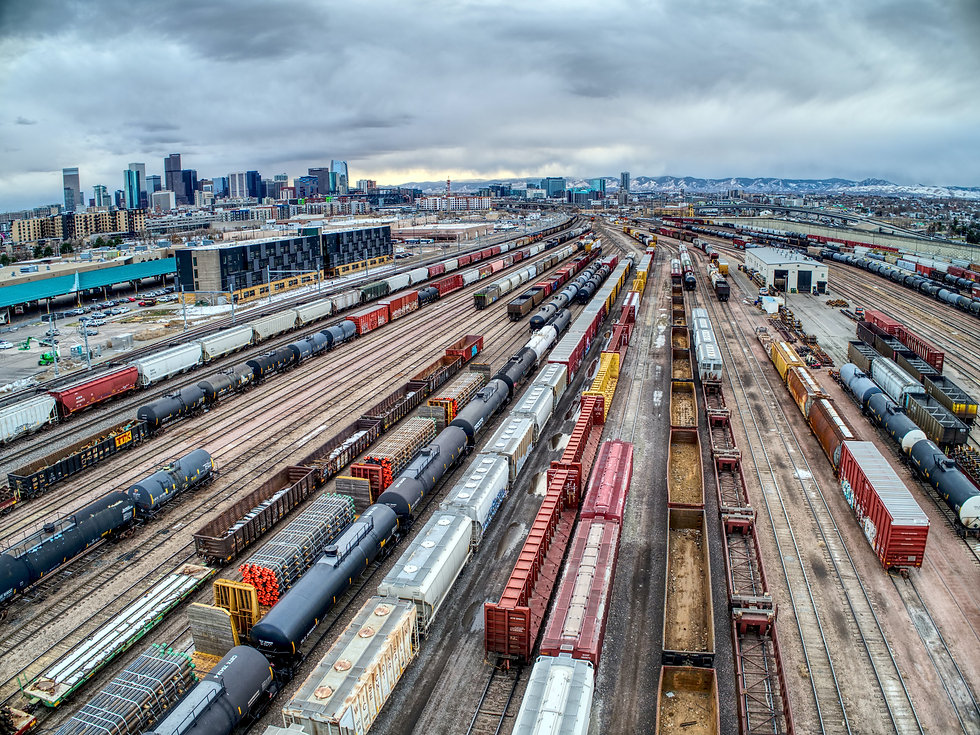 Aerial view of a rail yard with numerous railcars, tank cars, and hopper cars.