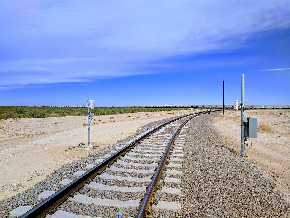 IN1500 Stationary AEI System in the foreground of a long line of railcars and a blue sky.
