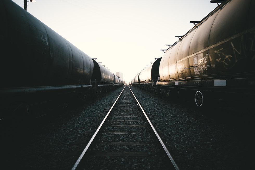 Railroad tracks going off into the distance in between two lines of tank cars.