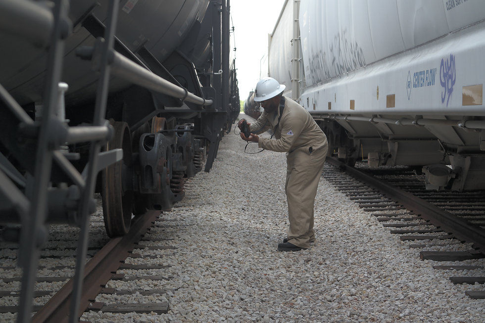 Rail operator scanning the tag on a railcar between two sets of tracks.