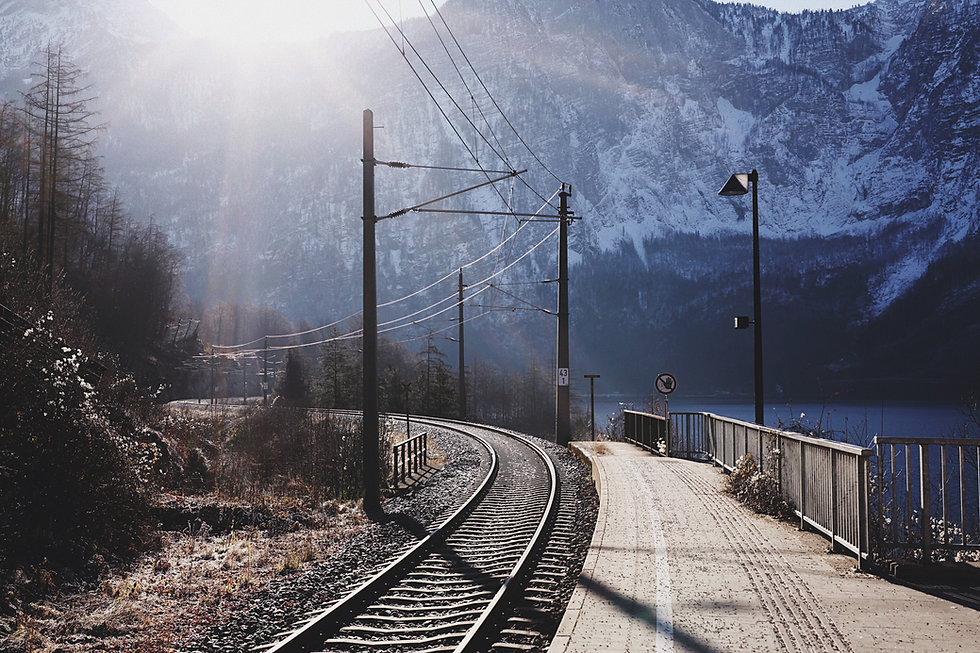 Winding railway at the foot of a snowy mountain.