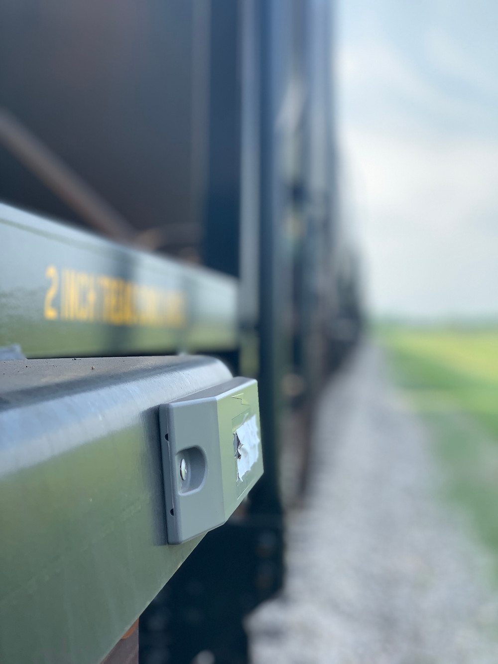 Automatic Equipment Identification (AEI) Tag in focus mounted on a railcar.