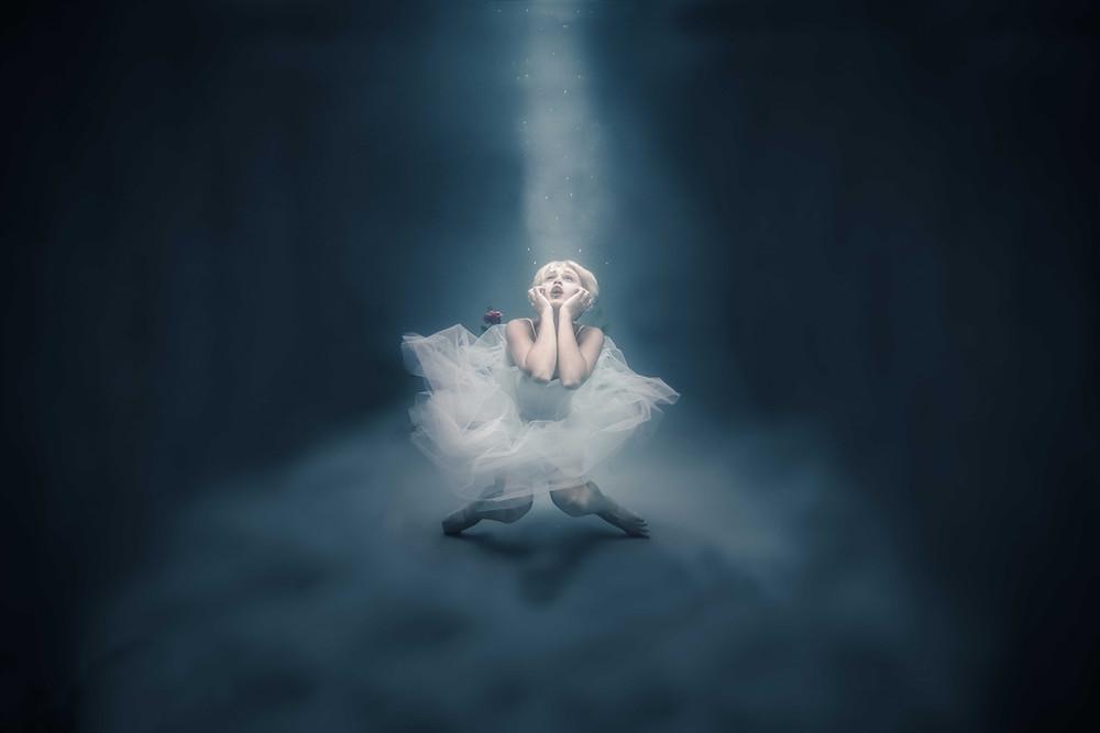 photographie d'une femme danseuse au fond d'une piscine sombre