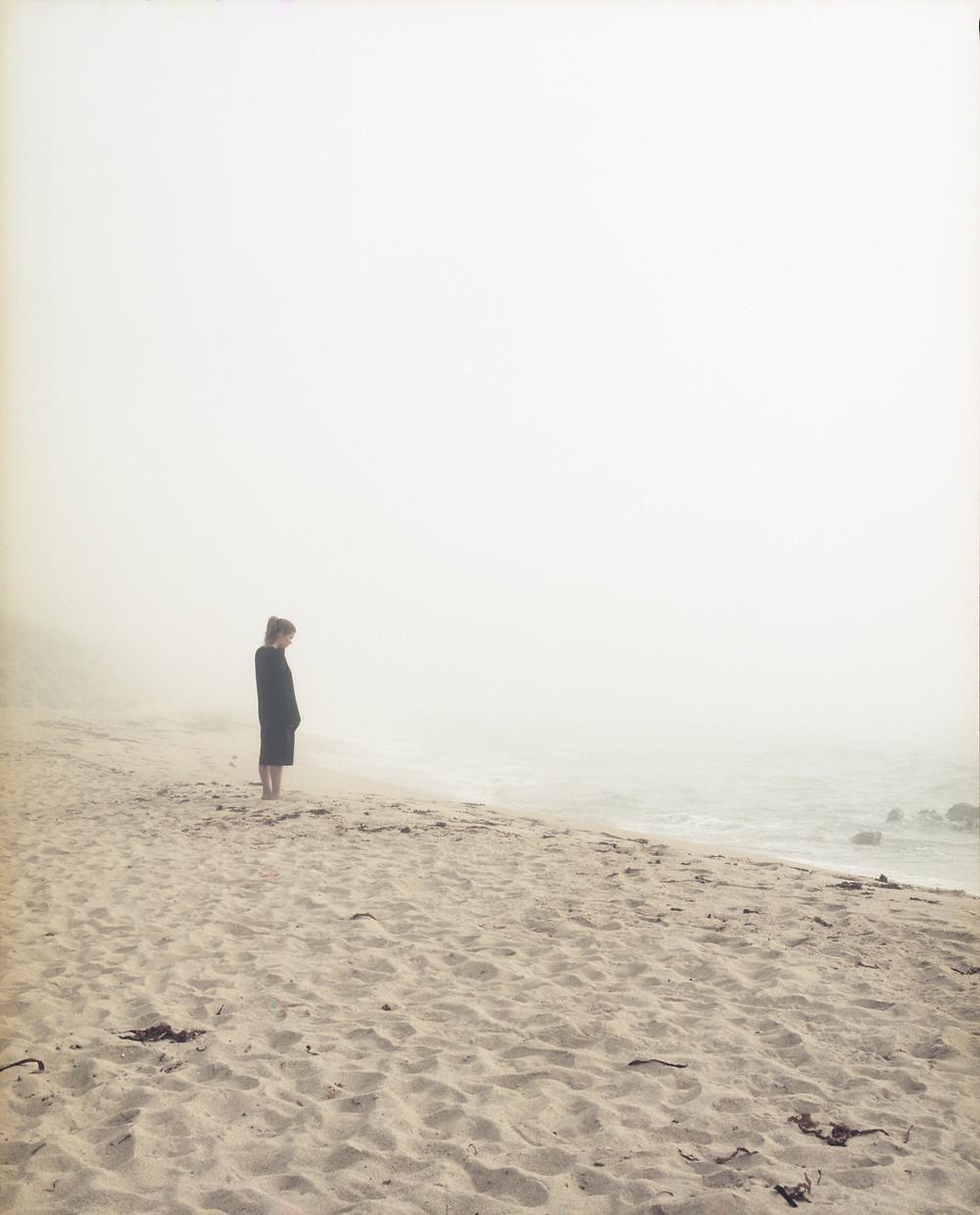 femme sur la plage regardant la mer noyée dans le brouillard