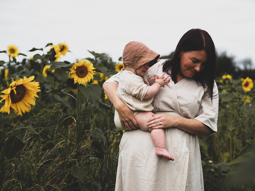 Mother and daughter in a field full of sunflowers