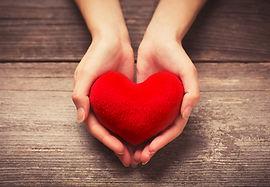 Female hands giving red heart.jpg