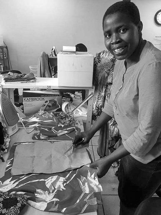 Alice working in our factory. One of the criteria for our first fashion incubation was for ladies to have basic sewing skills. Alice can now cut and sticth our Jasmine Wrap Dresses from scratch.