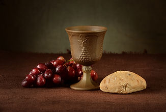 Wine cup surrounded by bread and grapes