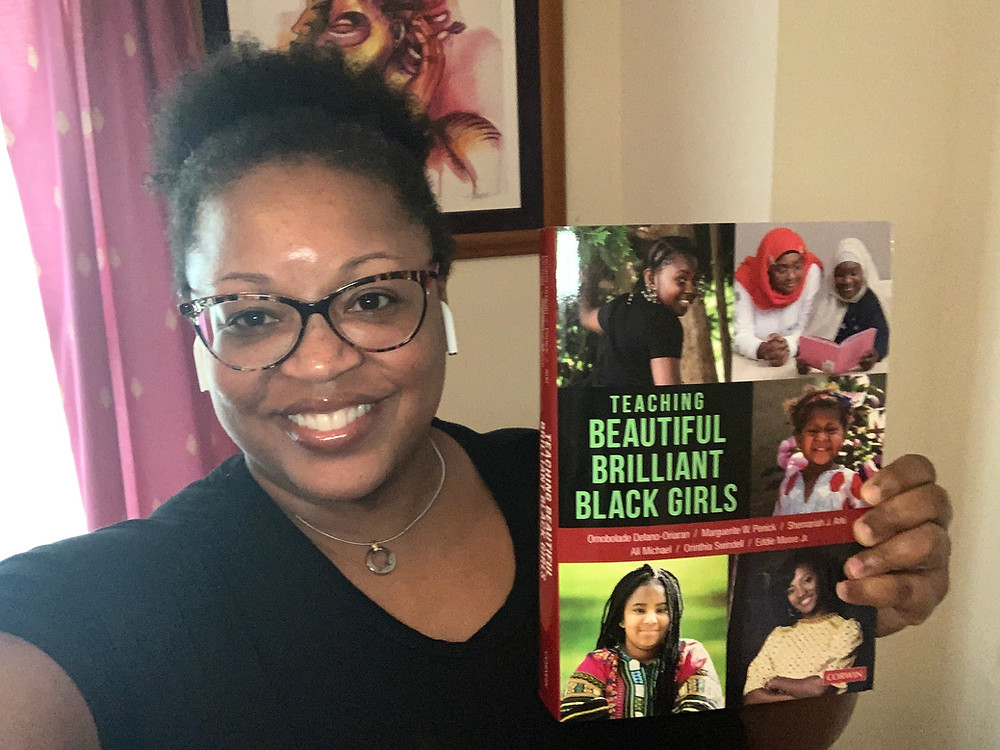 Dr. Bentley-Edwards is smiling and holding a copy of the book, Teaching Beautiful, Brilliant Black Girls