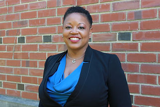 Image of Dr. Keisha Bentley-Edwards standing in front of a brick wall