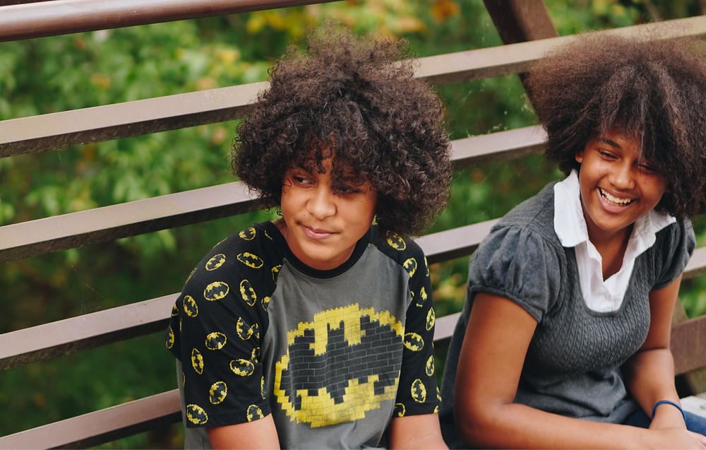 Two Black teenagers sitting on a bench, smiling.