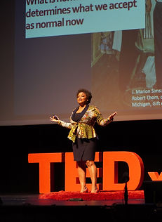 """Dr. Keisha Bentley-Edwards standing with her arms open wide while giving a talk for TEDxDuke 2021. In the is the partial image that states, """"What happened in the past determines what we accept as normal now."""""""