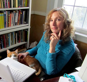 Annie Kuhn at her desk with cat on lap