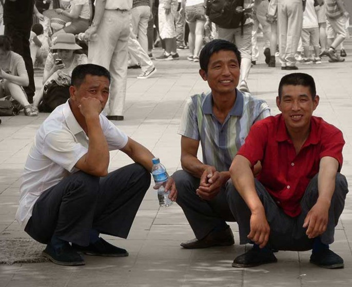 Asian men squatting