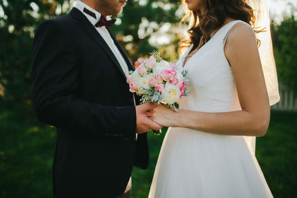 Bride and groom holding hands with flower bouquet