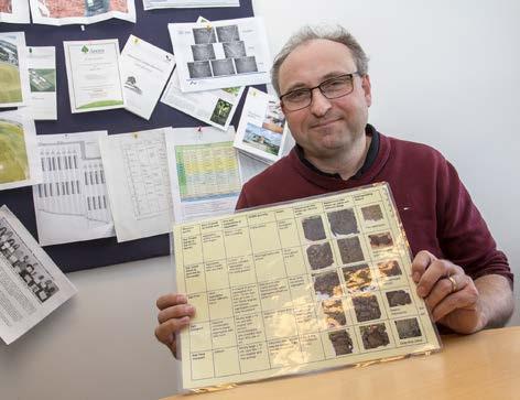 Lars J. Munkholm i sit kontor på Forskningscenter Center med det ark i hånden, som bruges til at vurdere jordstrukturen sammen med spadeprøver fra markerne.