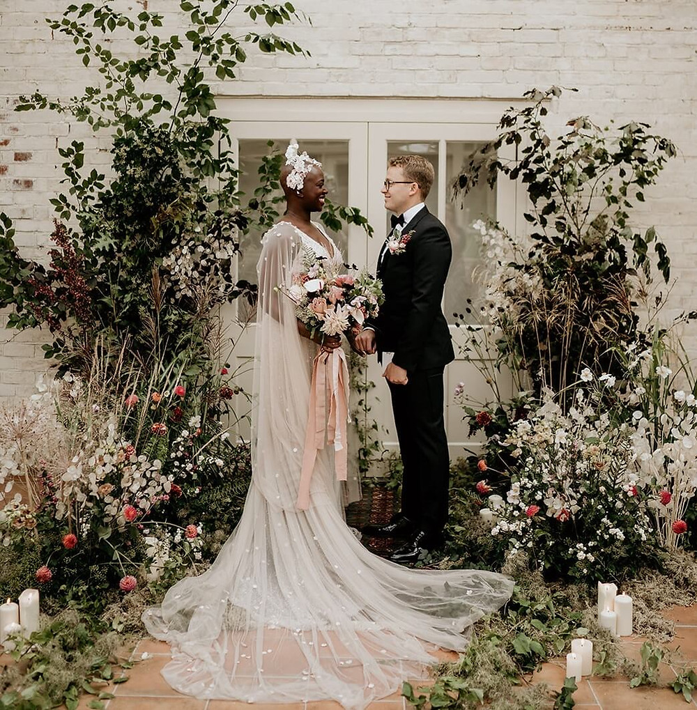 Bride and groom facing each other in front of a floral backdrop