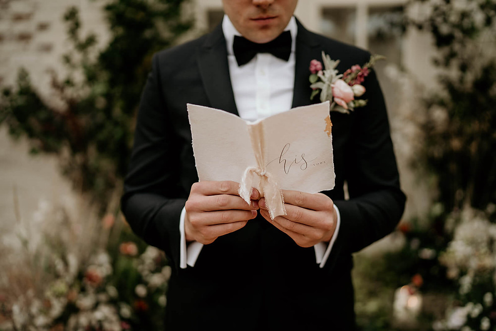 Groom wearing a suit and bow tie and holding a vow booklet