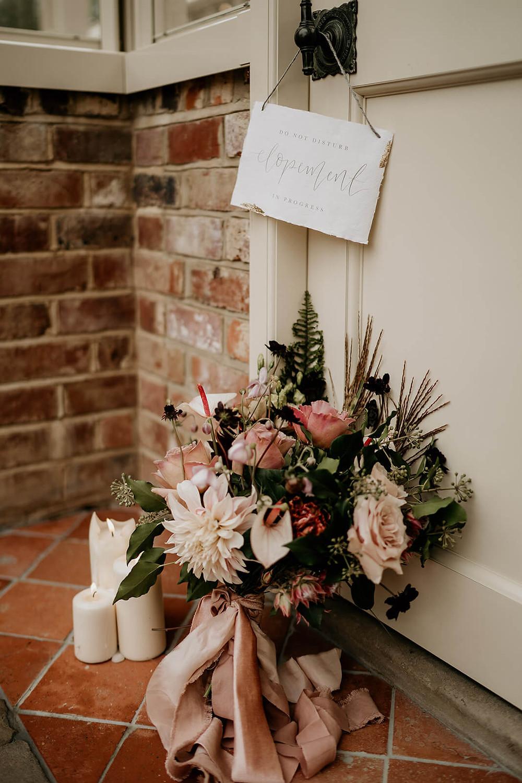 Autumnal bridal bouquet next to a do not disturb elopement sign