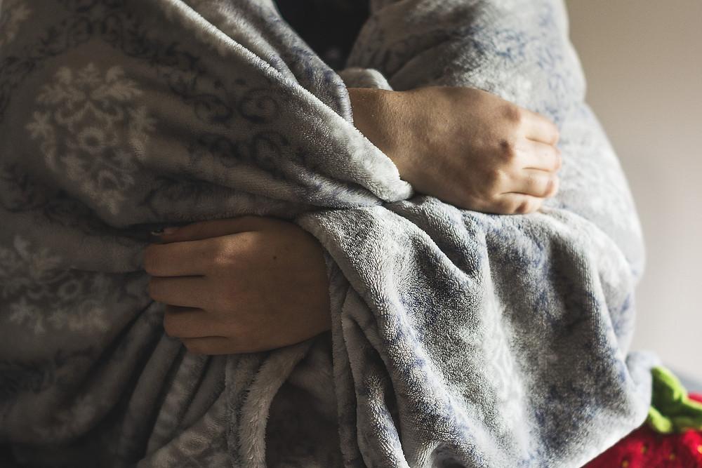 buste d'une personnes enroulée dans une couverture