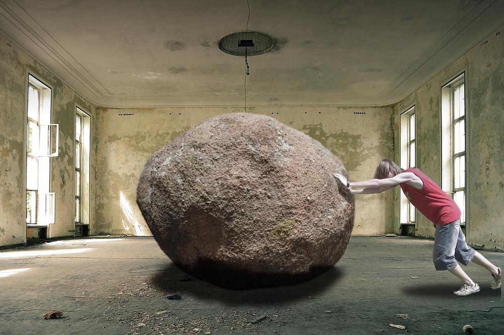 Homme poussant un énorme rocher dasn une pièce