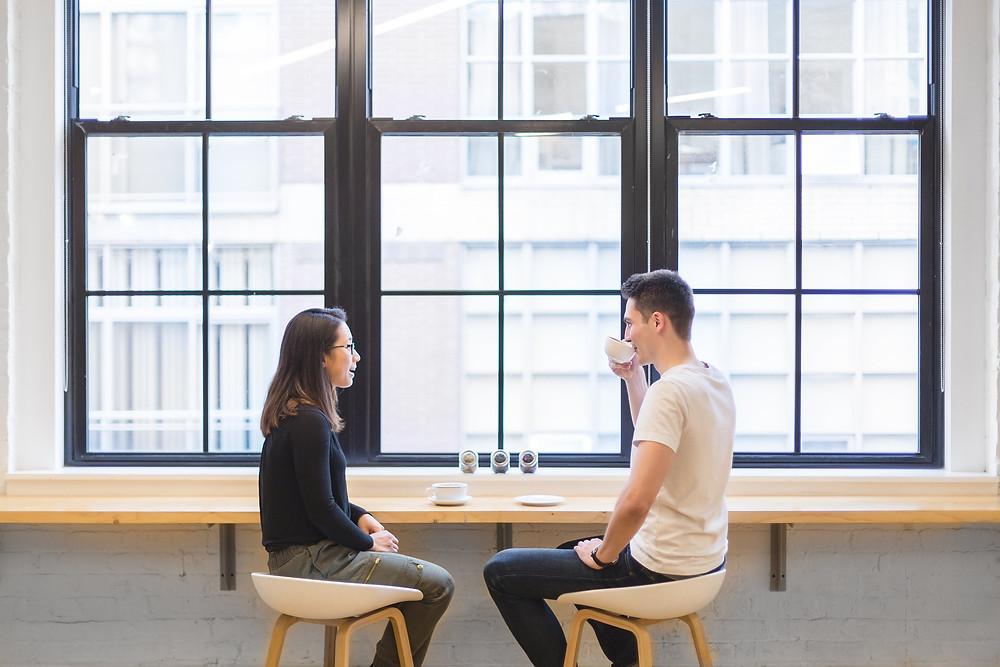 un homme et une femme discutent devant une grande fenêtre