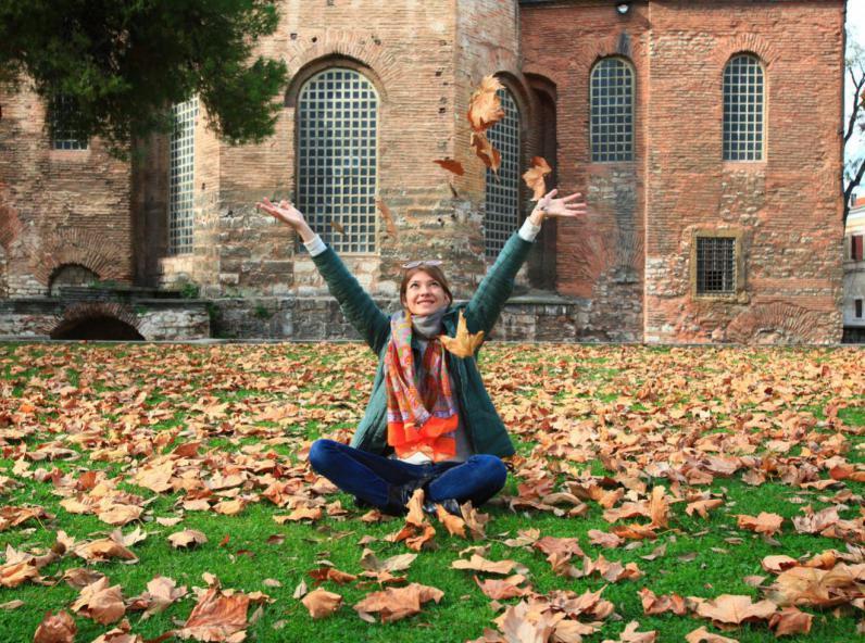 Femmes assise par terre lançant des feuilles mortes