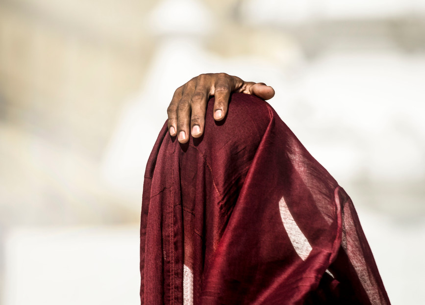 A young monk places a hand on his head as he prays