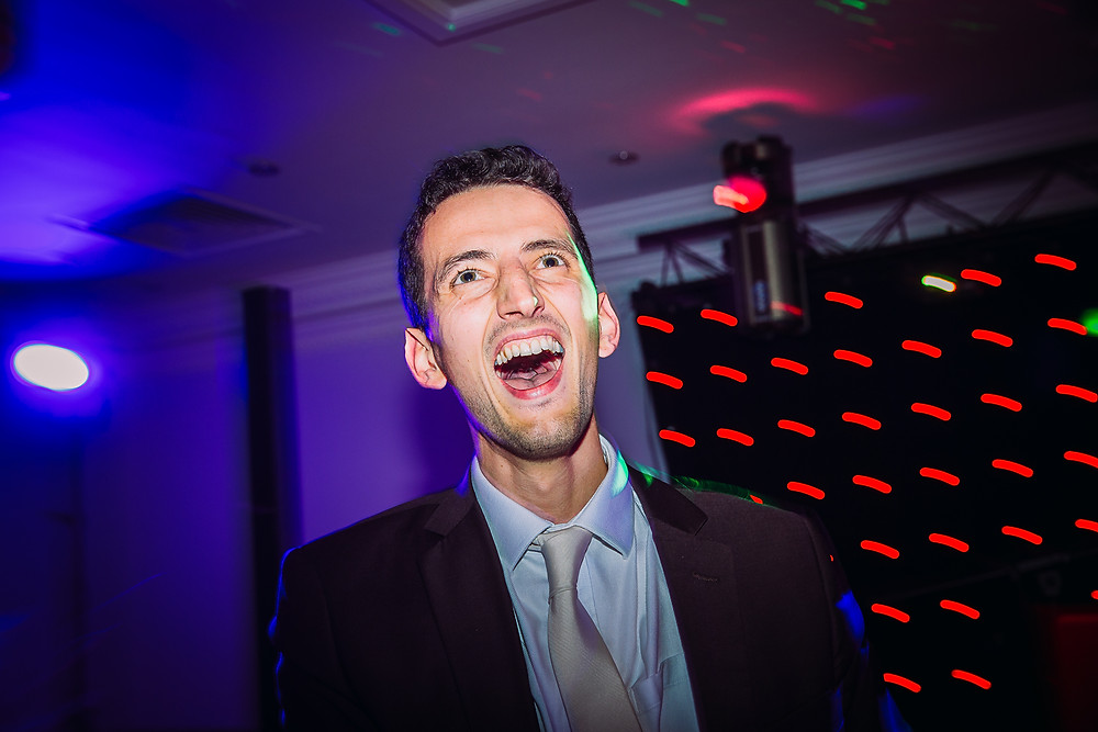 A man in a suit dances and his mouth is open in excitement