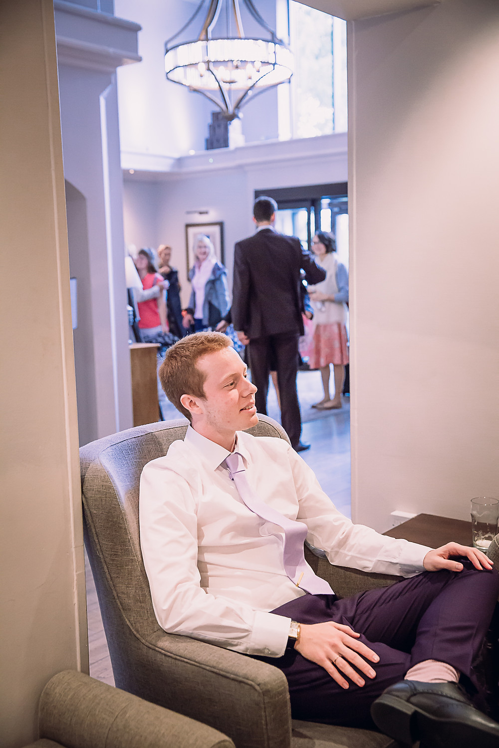 A groom sitting in a chair in a reception of a hotel, his bride has arrived behind him and is hugging a family member