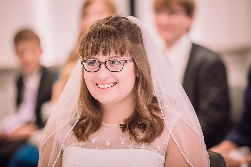 A  closeup of the bride, she wears a veil and glasses. The top of her dress is lace and embroidered