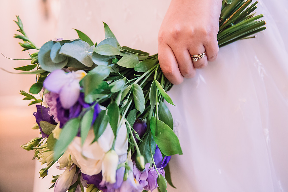 A closeup of the bridal bouquet held in the left hand, the hand has two rings on the fourth finger