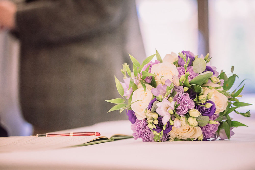 A bouquet with white and purple flowers, this sits next to the register book and pen