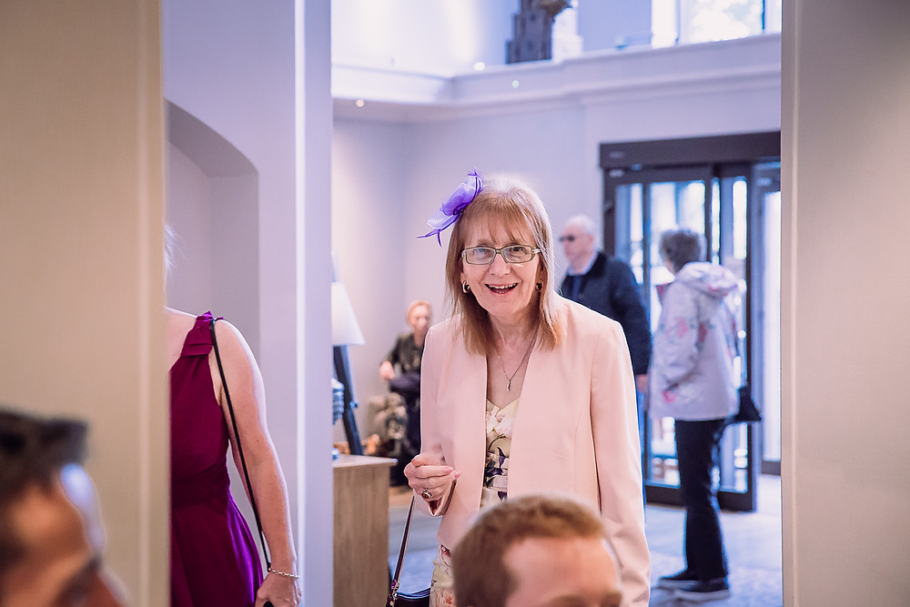 The mother of the groom looks excitedly at her son, she wears a pink jacket and purple fascinator