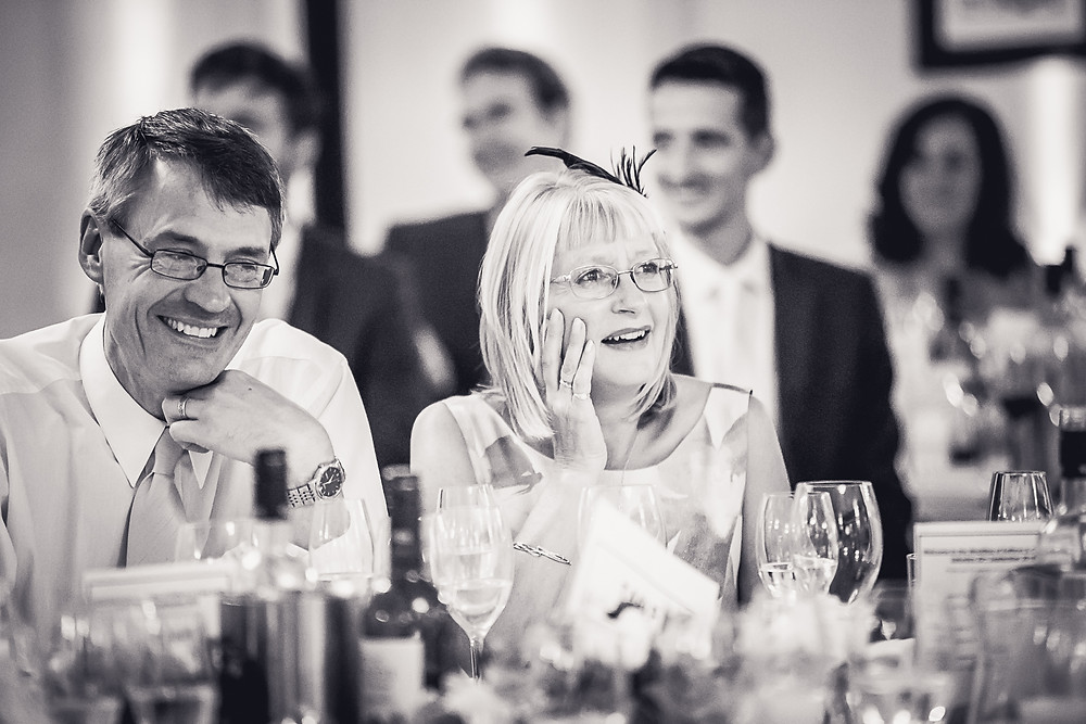 The mother of the bride looks shocked and holds her hand to her face, the father of the bride is laughing