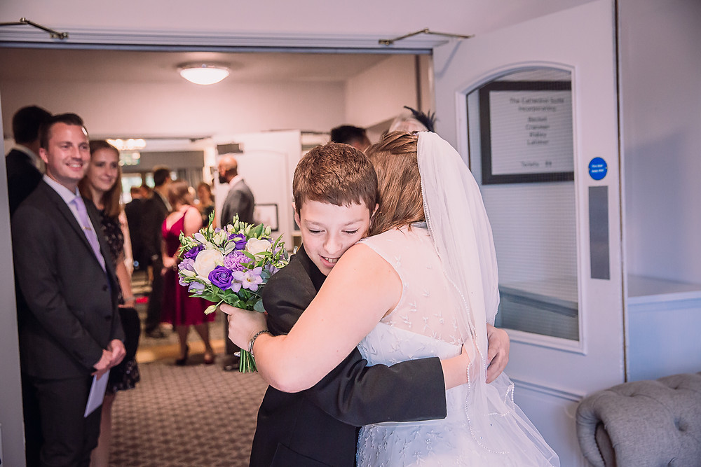 The bride hugs a guest who is a boy wearing a suit